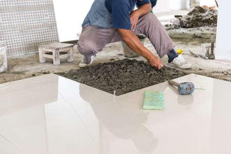 trabajador puesta baldosas ceramista en el suelo. Ceramista profesional está poniendo baldosas de cerámica en el piso Foto de archivo