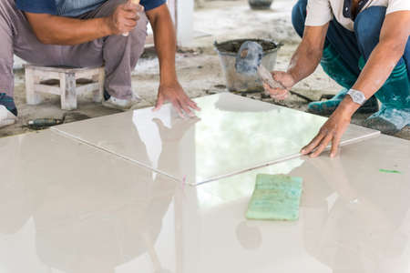 placing: worker putting ceramist tile on the floor. Professional ceramist is laying ceramic tile on the floor