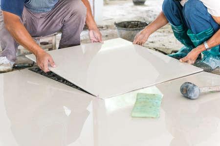 ワーカー置いて陶芸家は床をタイルします。プロの陶芸家は、セラミック タイルの床を敷設します。 写真素材