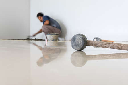 lavoratore di indossare tegola ceramista sul pavimento. Ceramista professionale si posa piastrelle di ceramica sul pavimento