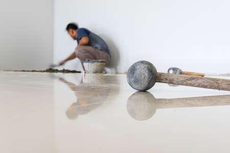 pegamento: trabajador puesta baldosas ceramista en el suelo. Ceramista profesional está poniendo baldosas de cerámica en el piso