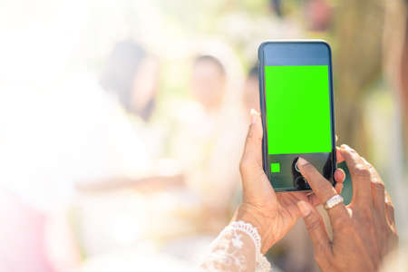 green screen: People use smart phone to take photographs in Thai wedding ceremony. (green screen at smart phones)