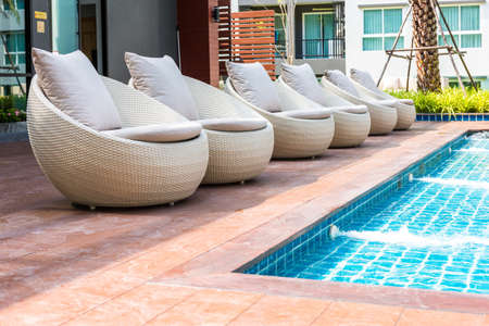 lounges: Lounges in side of swimming pool Stock Photo