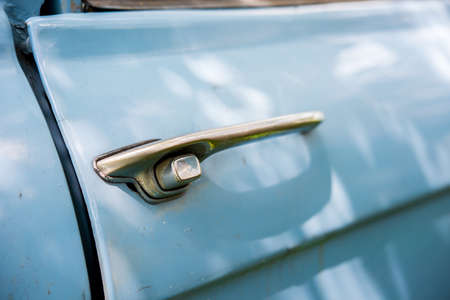 Old chrome car door handle bar close up image on rusty body vintage car Stock Photo - 58625522