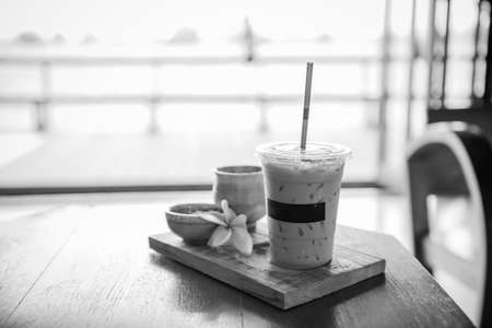 decaffeinated: black and white of Ice coffee and some biscuits on the table
