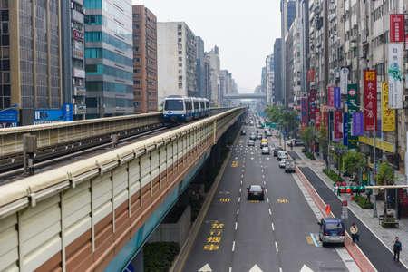 台北 (台湾)-2017 年4月2日: オフィスタワーとブルークリアスカイの間にある台北地下鉄システムの高架上を走行する列車の眺め ~ 台湾の首都台北にあ 報道画像