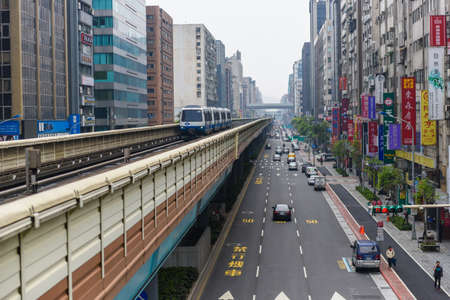 Taipei, Taiwan - April 2, 2017:View of a train traveling on elevated tracks of Taipei Metro System between office towers under blue clear sky ~ View of MRT railways in Taipei, the capital city of Taiwan.