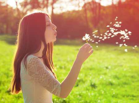young woman blowing on a white dandelion photo