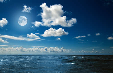 sea in the horizon: full moon over the ocean Stock Photo