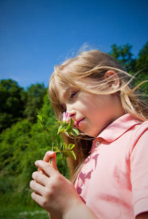 smelling: young girl smelling pink blossom
