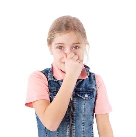 niños malos: chica tapándose la nariz a causa de un mal olor Foto de archivo
