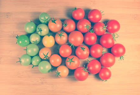 ripe and unripe grape tomatoes on a wooden background 免版税图像