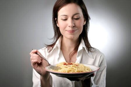 pasta fork: A young woman with a plate of pasta Stock Photo