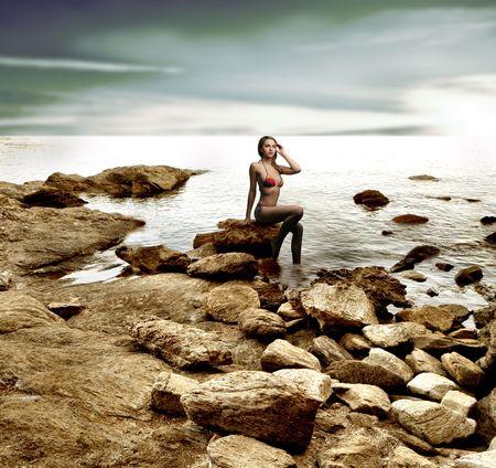 Eine schöne Frau auf dem Felsen am Meer