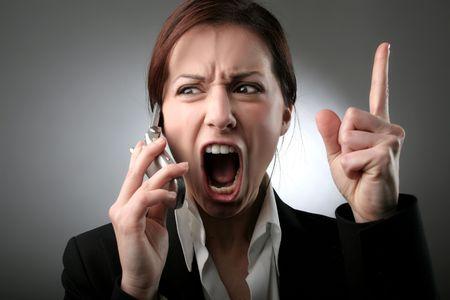enojo: Una mujer gritando en el tel�fono  Foto de archivo