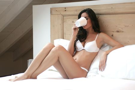 A beautiful woman on the bed with a cup photo