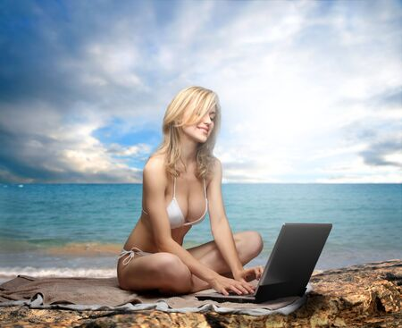 a girl on the beach with a laptop