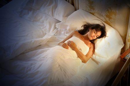 mujer en la cama: una mujer dormir en la cama en la noche Foto de archivo