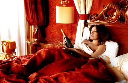 sexy woman in a luxury bedroom with a bottle of champagne photo