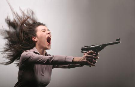 persona enojada: hermosa chica gritando y la celebraci�n de un arma de fuego