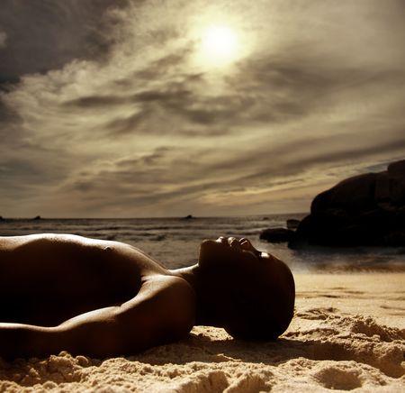 black man laying on the beach  photo