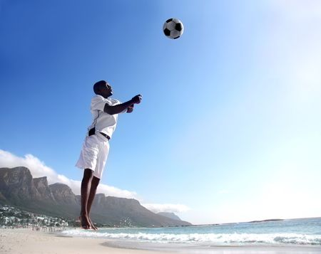 african soccer or football player heading ball on the beach photo