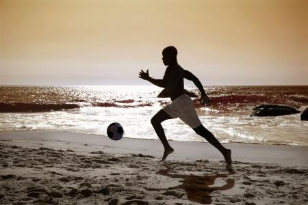 football silhouette: african soccer o giocatore di football calci palla sulla spiaggia