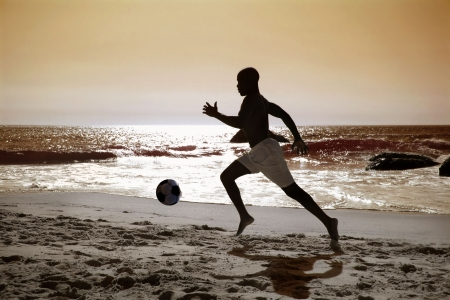 african soccer or football player kicking ball on the beach