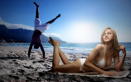 a beautiful caucasian woman looking a black boy doing exercise on the beach  photo
