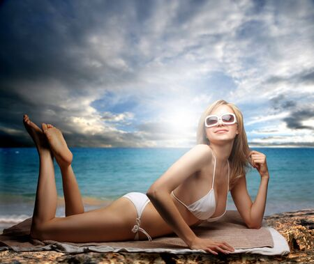 woman in towel: beautiful woman in bikini laying on the beach Stock Photo