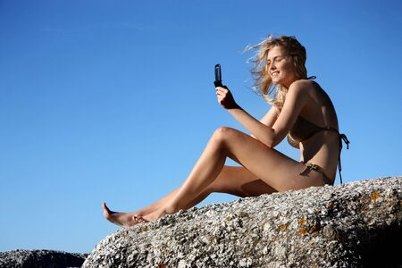 sexy pictures: young woman taking a picture with mobile phone on a sea rock