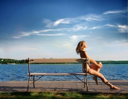 attractive girl in bikini sitting on a bench along the sea Stock Photo - 5484329
