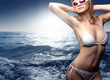 personas tomando agua: mujer hermosa con lentes de sol en bikini en el mar