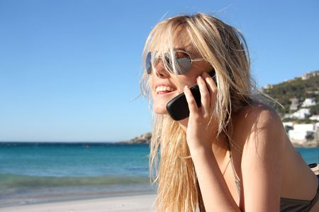 calling on phone: blond girl at mobile phone on the beach Stock Photo