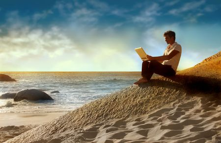 men using laptop in a enchanting sea scape at the sunset