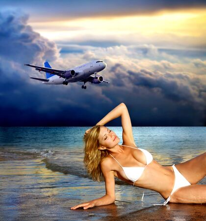 water jet: sexy girll on the beach and a flying airplane on the background Stock Photo