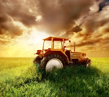 tractor in a grass field at the sun dawn photo