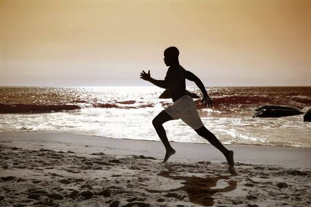 black man running along the beach photo