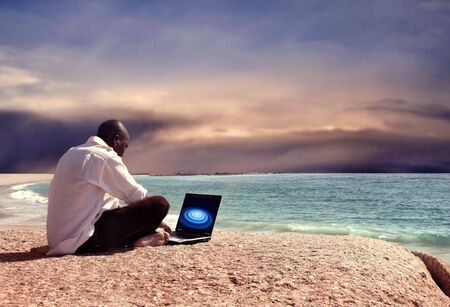 back screen: black man with laptop on the beach