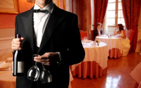 waiter with bottle and wine and a couple of newleywed photo