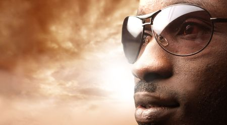 closeup of black man wearing sunglasses against a cloudy sky photo