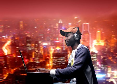 arte africano: chico joven africano descarga de m�sica de la computadora port�til con vista a la ciudad en la backgroung