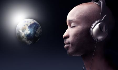 musica electronica: hombre negro escuchando m�sica y un planeta Tierra en el fondo
