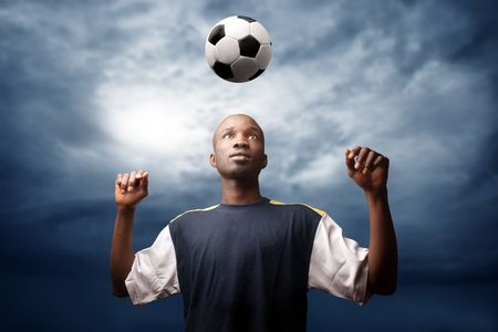 afrcican soccer player heading a ball in a stormy weather Stock Photo - 5592635
