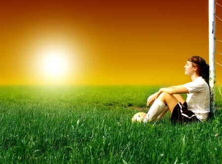 female soccer: female soccer or football player sitting against a goal door in a grass field