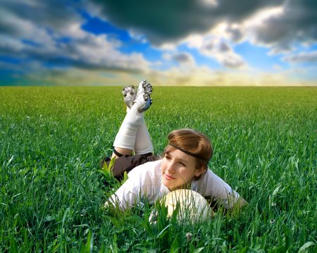 female soccer or football player lying in a grass field photo