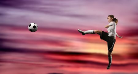 female soccer or football player kicking the ball Stock Photo