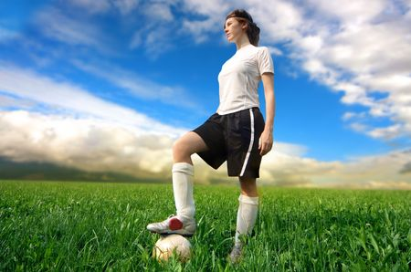 action shot: soccer or football female player standing in a grass field