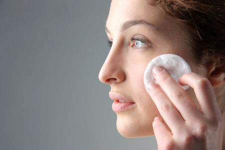 make up products: woman cleaning face with cotton disk Stock Photo
