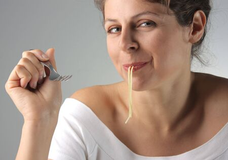 young woman eating pasta photo